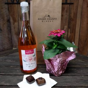 bottle of wine, two chocolates, and a flower